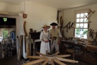 Phill and Emily in period outfits in the colonial Williamsburg Wheelwright's Shop