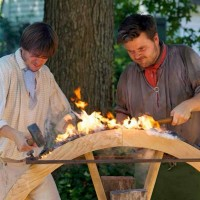Master wheelwright Phill Gregson and Andre De Lisle nailing strakes to traditional wooden canon wheels