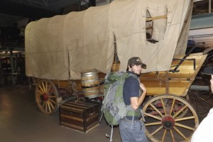 Wheelwright Phill Gregson with traditional covered Contestoga wagon in Remington museum